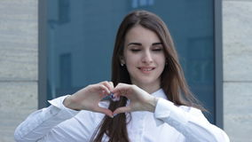 Business Lady shows hands symbol of the heart and smiling. Charming business Lady shows hands symbol of the heart and smiling stock footage