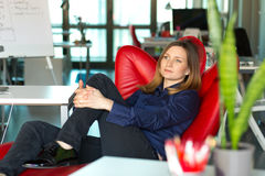 Business Lady sitting in red Chair at modern creative Office. Business Lady in smart casual Clothing sitting in Relaxation Chair and thinking about strategic Stock Photography