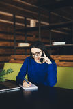 Business lady speak on phone and make notes at work table. In office hub Stock Photo