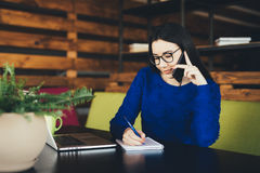 Business lady speak on phone and make notes at work table. In office hub Stock Photography