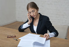 Business lady speaking on the phone and checks the report sittin. G at the desk. glasses and pen next to her Stock Photography