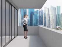 Business lady is standing on the balcony of the skyscraper and looking at the new business perspectives. Singapore panoramic. Young business lady is standing on Royalty Free Stock Photography