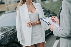 Woman taking with worker near car outside stock images