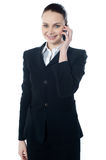 Business lady talking on phone. Mature businesswoman talking on mobile phone looking at you Royalty Free Stock Images