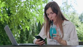 Business Lady Talking on the Phone. In front of an open laptop. Drinking smoothie. Medium shot. Soft Focus Royalty Free Stock Photos