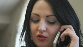 Business lady talks on the phone in cafe stock video footage