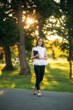 Business lady uses a tablet in the park during a break. Business woman in the park Royalty Free Stock Photography