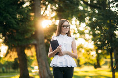 Business lady uses a tablet in the park during a break. Business woman in the park Royalty Free Stock Photo
