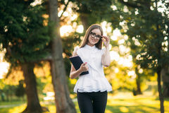 Business lady uses a tablet in the park during a break. Business woman in the park Royalty Free Stock Image