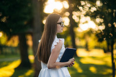 Business lady uses a tablet in the park during a break. Business woman in the park Royalty Free Stock Photos