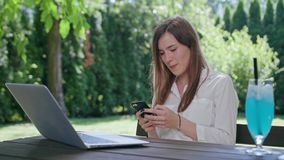 Business lady using a phone. In front of an open laptop. Medium shot. Soft Focus stock video