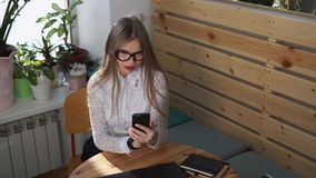 Business lady is watching news on her smart phone during lunch break. Business lady with long hair looks funny pictures on her smart phone during lunch break stock video