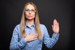 Business lady wearing blue glasses making oath gesture stock photos