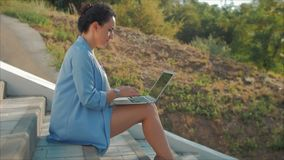 Business Lady Working on the Laptop, Attractive Brunette in a Blue Suit With a Laptop, attractive woman working on her. Computer on outdoors stock footage