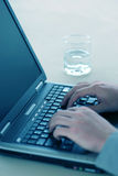 Business laptop. Business Man types away on his laptop with a glass of water on the table Stock Photo
