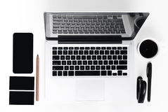 Business laptop, phone and a coffee on the white table. Business laptop, phone and a fresh morning coffee on the white table background Royalty Free Stock Images