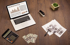 Business laptop with stock market report on wooden desk Royalty Free Stock Image