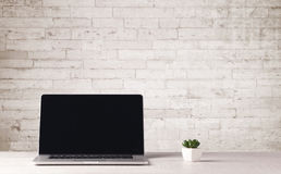 Business laptop with white brick wall Stock Photo