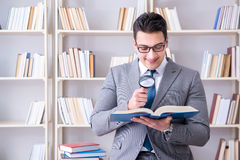 Business law student with magnifying glass reading a book. Businessman student reading a book studying in library Royalty Free Stock Photography