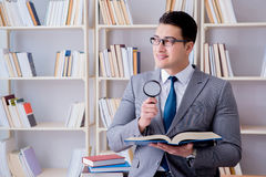 Business law student with magnifying glass reading a book Royalty Free Stock Images