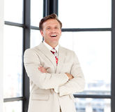 Business leader with folded arms smiling at the ca. Serious business leader with folded arms smiling at the camera royalty free stock photo