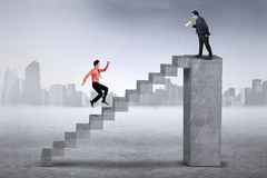 Business leader and his subordinate. Young businessman yelling to his employee from the top for running faster on the stair Stock Image