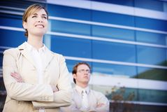 Business leaders. Business woman and man taking charge in front of a blue building Stock Image