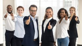 Business leaders with employees showing thumbs up looking at camera stock images