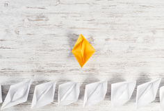 Business leadership concept. Set of origami boats on wooden table Stock Photos