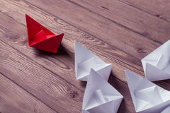 Business leadership concept with white and color paper boats on Royalty Free Stock Photos
