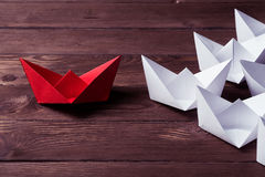 Business leadership concept with white and color paper boats on Royalty Free Stock Images