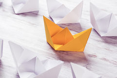 Business leadership concept with white and color paper boats on Stock Photo