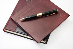 Business leather agendas in a pile with a golden pen Royalty Free Stock Photos