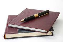 Business leather agendas in a pile with a golden pen Royalty Free Stock Photo