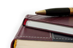 Business leather agendas in a pile with a golden pen Royalty Free Stock Images