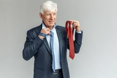 Business Lifestyle. Businessman standing isolated on gray choosing tie smiling pensive stock photo