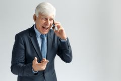 Business Lifestyle. Businessman standing on gray shouting at phone irritated stock photo