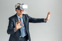 Business Lifestyle. Businessman in virtual reality headset standing isolated on gray playing game smiling cheerful. Senior business man wearing virtual reality stock photo