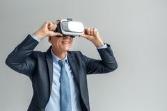 Business Lifestyle. Businessman in virtual reality headset standing isolated on gray watching video happy. Senior business man wearing virtual reality headset stock image