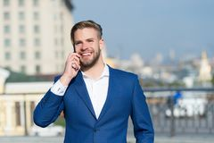 Business lifestyle concept. Happy businessman with smartphone on sunny terrace. Man smile in formal suit with mobile phone outdoor. Business communication and Stock Images