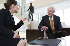 Business lobby meeting to review paperwork. Royalty Free Stock Photo