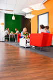 Business lounge. Modern styled, colorful business lounge, with several project teams sitting at tables during informal meetings Stock Images