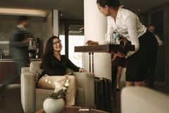 Business lounge staff serving coffee to female traveler Royalty Free Stock Photography