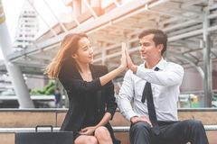 Business lover couple hi five for success sitting outdoor stock images