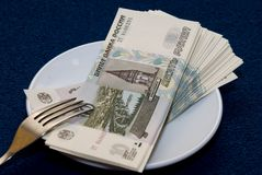 Business-lunch. Bundle Russian money is on the plate Royalty Free Stock Images