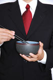 Business lunch. Man in black suit wearing red power tie eating with chopsticks from a japanese rice bowl stock images