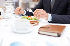 At business lunch. Close-up of businessman hands holding knife and fork over vegetable salad during business lunch Stock Photo