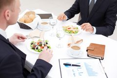 Business lunch. Close-up of businessmen sitting in cafe and having business lunch Stock Photos