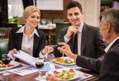 Business lunch. Confident business partners in suits discussing contract during business lunch Stock Photo