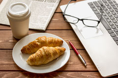 Business lunch with croissant and laptop on wooden desk Royalty Free Stock Photography